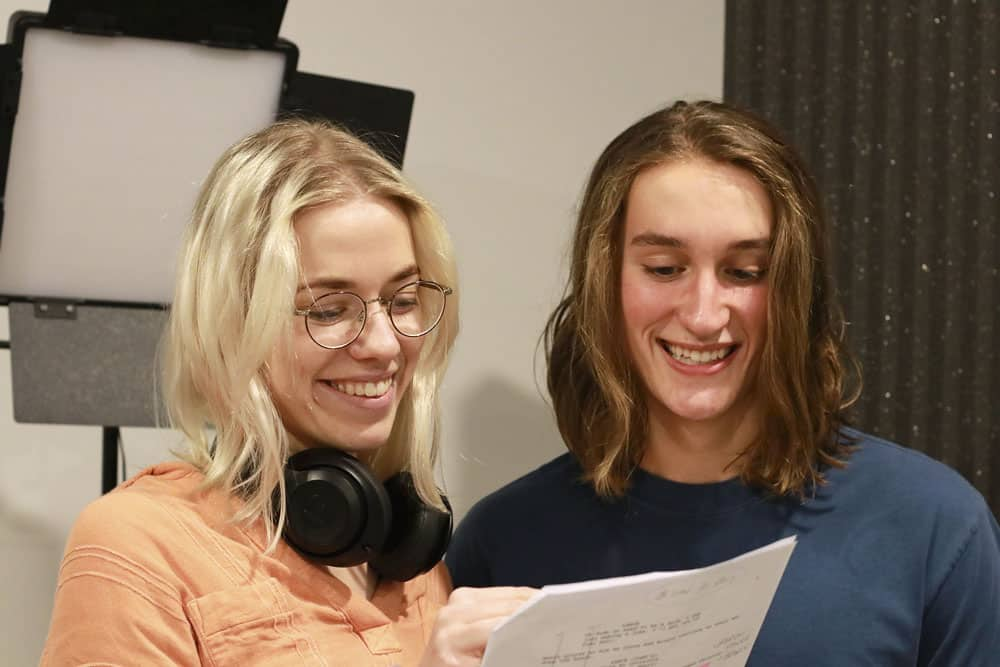 Two people standing side by side smiling looking at a piece of paper. The person on the left is a female with blonde hair and glasses and on the right is Darcy Halliday who has brown shoulder length hair.