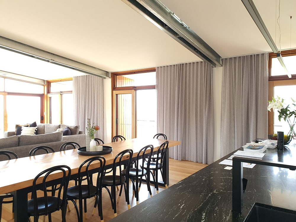 Wooden dining table with grey curtains hanging on window