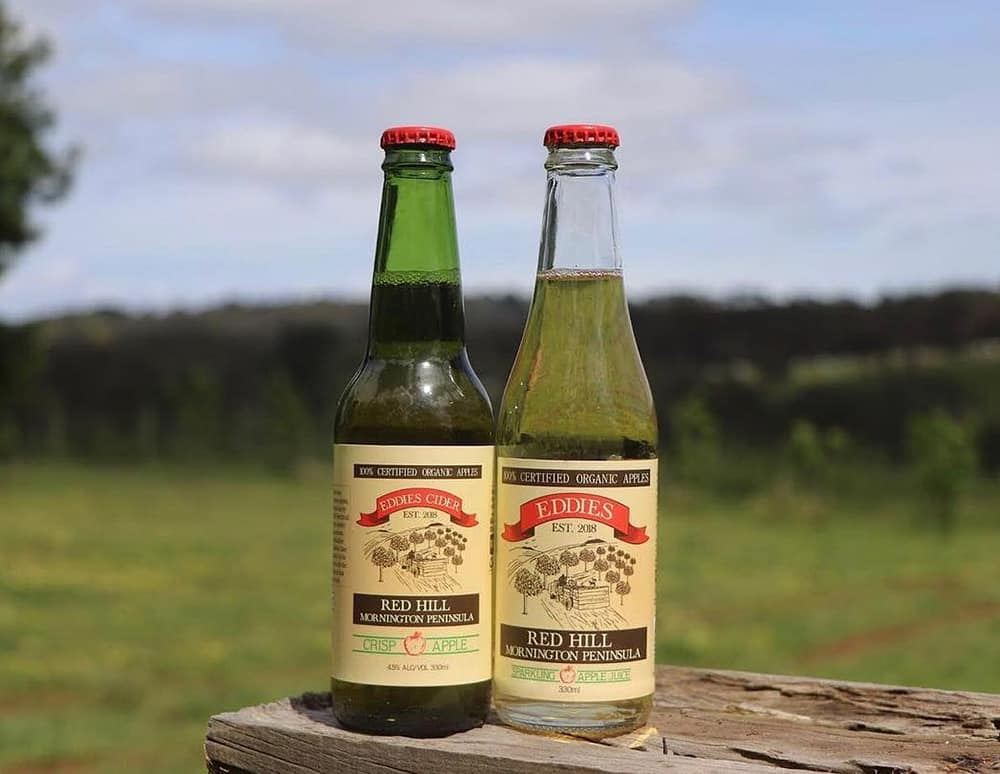 Two bottles of Eddies Organic Cider in front of a grass pasture