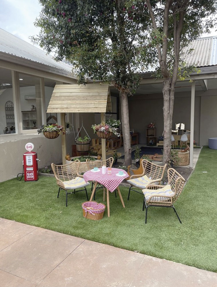 Outdoor area of a child care called Seaford house of early learning setting with a cute child's play area set up on green grass.