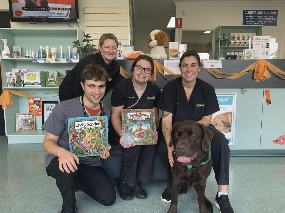 Five people standing around with a book with two books next to a brown labrador.