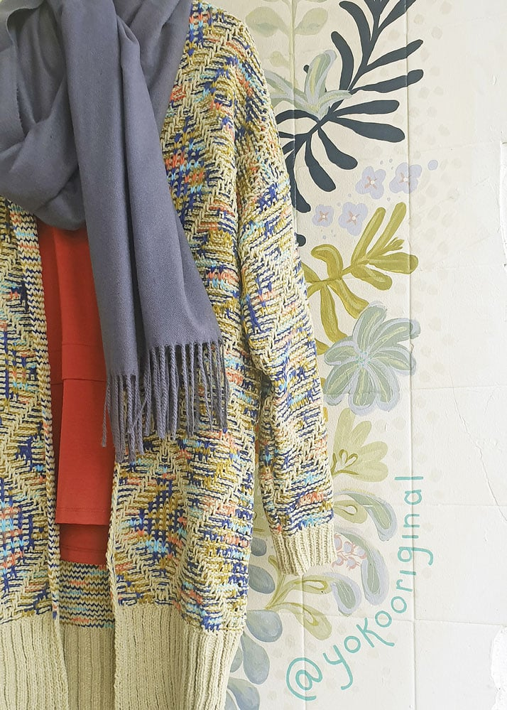 YoKo Original Knit Fashions. A knitted blue scarf and floral knitted cardigan on a floral wall in store.