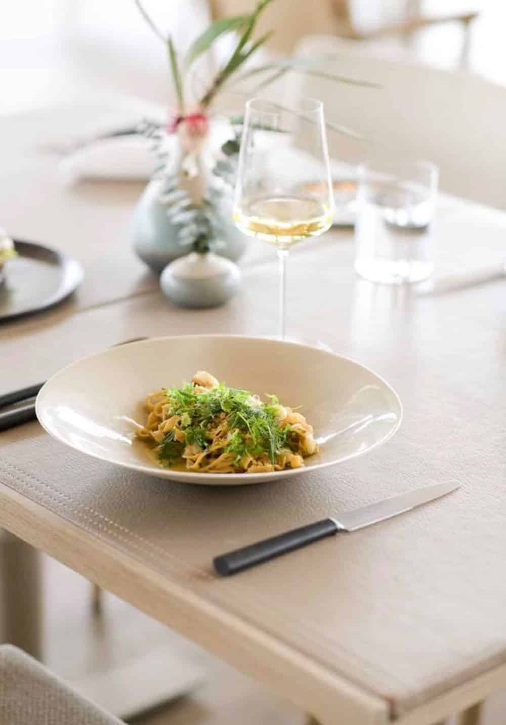 Pt. Leo Estate Wine and pasta with micro greens as garnish served in white bowl on wooden table