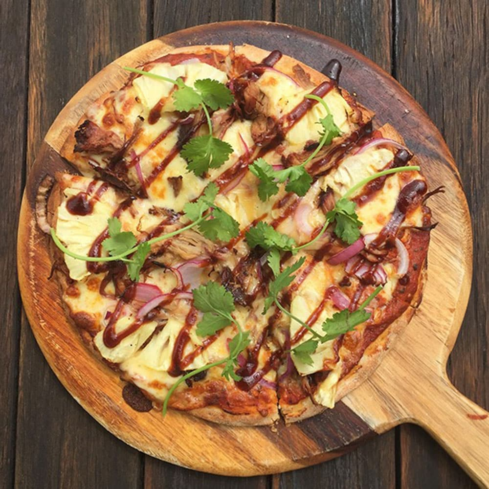Pizza with red onion, cheese, chicken and sauce drizzle sitting on wooden serving board
