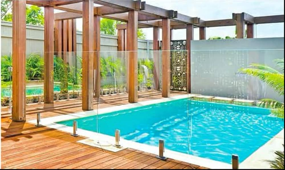 Pool with surrounding glass fencing with brown wooden deck